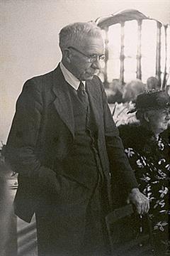 Sir Walter Murdoch standing behind a chair