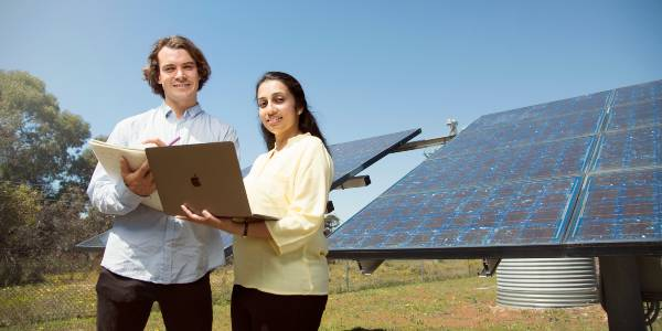 a male and a female student looking at a laptop with solar panels in the background