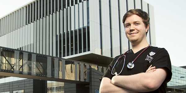 Medical student posing in front of hospital
