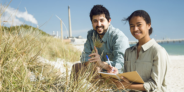 Two students by the beach studying flora