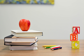 teachers desk with books and apple