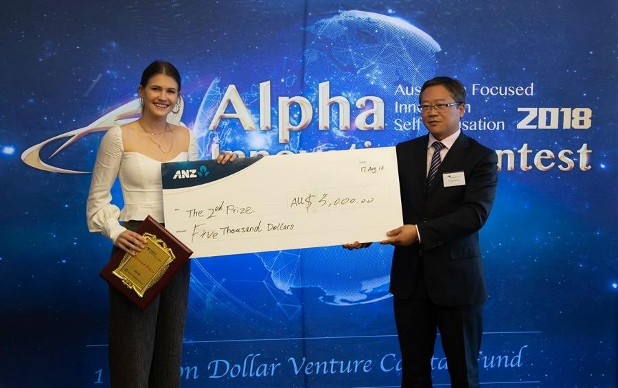 Morgan Becker receiving a prize at the Alpha Innovation Experience contest