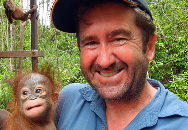Stephen Van Mil holds a smiling baby Orangutan while another hangs from a pole in the background